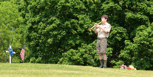 Boy scout plays tap on memorial day Stock Photo
