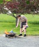 Boy scout que retiran banderas viejas en Memorial Day Foto de archivo libre de regalías