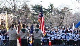 Boy scout que sostienen las banderas para el compromiso de la lealtad foto de archivo libre de regalías