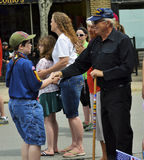 Boy Scout Shakes Hand of Veteran at Parade Royalty Free Stock Image
