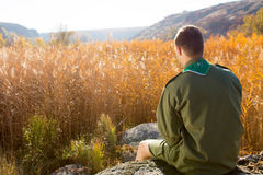 Boy Scout Sitting on the Rock Watching Brown Field. Rear View of White Boy Scout Sitting on the Huge Rock Alone Watching the Wide Brown Field on an Autumn Season Stock Photos