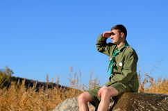 Boy Scout Sitting on Rock Watching Over the Field. Young Boy Scout in Uniform Watching Over the Brown Field on A Sunny Day While Sitting on the Boulder Stock Photo