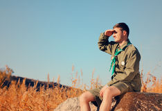 Boy Scout Sitting on Rock Watching Over the Field Royalty Free Stock Photos