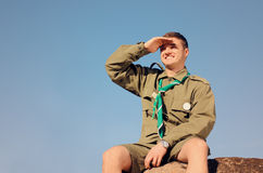 Boy Scout Sitting on Rock Watching Over the Field Royalty Free Stock Images