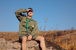 Boy Scout Sitting on Rock Watching Over the Field Stock Images