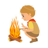 Boy scout squatting near the bonfire, a colorful character Stock Photos