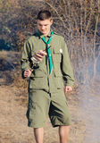 Boy Scout with Stick of Sausages by Campfire Stock Photo