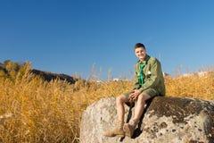 Boy scout su grande roccia all'area di campo Immagine Stock