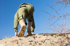 Boy scout in uniforme che scala una grande roccia fotografia stock