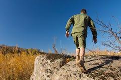 Boy scout Walking en roca grande vieja en el área de campo Imagenes de archivo