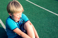 Boy with a scraped knee. Outdoor. Wound on boy knee after accident stock photos
