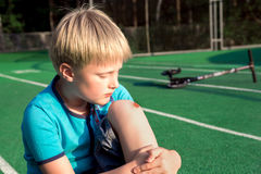 Boy with a scraped knee. Outdoor. Wound on boy knee after accident stock photo