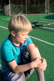 Boy with a scraped knee. Outdoor. Wound on boy knee after accident stock images