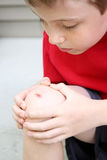 Boy with a scraped knee Stock Photos