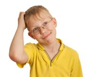 Boy scratches his head in puzzlement or confusion. As if pondering a deep question. Over white background Royalty Free Stock Photo