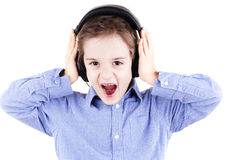 Boy is screaming when is listening to music. By headphones Royalty Free Stock Photo
