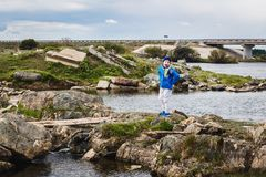The boy screams in blue sneakers and a blue windbreaker stands on a rocky river in the spring. Six-year-old boy screams royalty free stock images