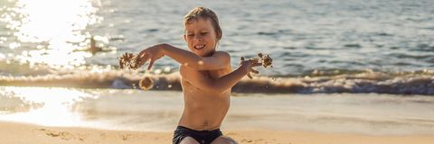 The boy screams and freaks out on the beach, throws sand. Tantrum concept BANNER, LONG FORMAT. The boy screams and freaks out on the beach, throws sand. Tantrum royalty free stock image