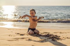 The boy screams and freaks out on the beach, throws sand. Tantrum concept.  royalty free stock photo
