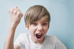 Boy screams and jokingly threatens with his fist Stock Images