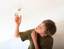 Boy screwing bulb. Concentrated boy screwing bulb on a lamp Royalty Free Stock Photos