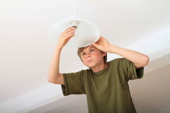 Boy screwing bulb. Concentrated boy screwing bulb on a lamp Stock Photography