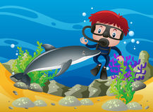 Boy scuba diving under the ocean with dolphin Stock Photo
