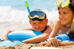 Boy in scuba mask on the sea beach with a friend. Portrait of boy and his friend on the beach on inflatable matrass wearing scuba mask laying near the sea royalty free stock image