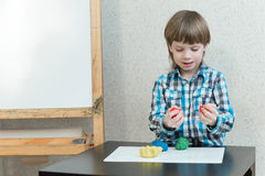 Boy sculpts from plasticine at home Stock Photography