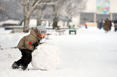 Boy sculpts snowman Royalty Free Stock Photo