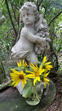 Boy sculpture and blooming sunflower in the bright  garden Stock Photos