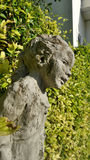 Boy sculpture in the garden unnder summer sun light Royalty Free Stock Photo