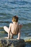 The boy on the sea. The child plays on a stone beach Stock Photos