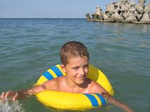 Boy in the sea. Boy with yellow swimming ring in the sea Stock Photos