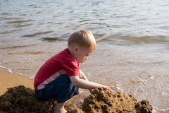 Boy and sea. The little boy plays sand at the sea Stock Images