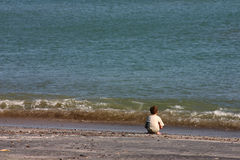 The boy and the sea. A solitary boy watching the sea royalty free stock photography