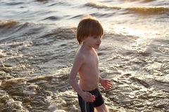 Boy in the sea foam at sunset Stock Photography