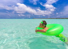 Boy in sea with inflatable Stock Photos