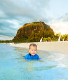 Boy in a sea. Le Morne on background Stock Photos