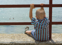 Boy and sea. The little boy sits on a pier holds on to the banister and looks in water royalty free stock images