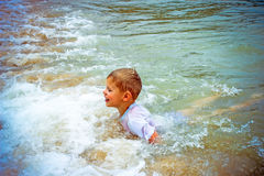 Boy at the sea lying in sand and waves Royalty Free Stock Photos