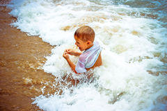 Boy at the sea lying in sand and waves Stock Image