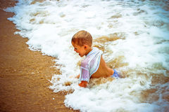 Boy at the sea lying in sand and waves Stock Images