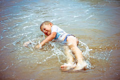 Boy at the sea lying in sand and waves Royalty Free Stock Image
