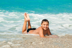 Boy at the sea lying on the sand and waves stock images