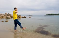 Boy.sea.mobile. The young man talks on mobile and by a leg(foot) does(makes) sparks on water Royalty Free Stock Image