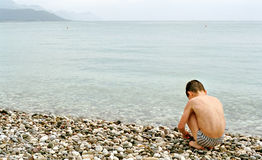 Boy, sea and pebble. Boy sitting on the beach Royalty Free Stock Photo