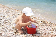The boy by the sea plays the cook. Little boy plays with enthusiasm by the sea Royalty Free Stock Image