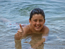 Boy in sea showing thumbs up sign. Portrait of a young  handsome smiling teenager boy lying in the Adriatic  sea in shallow water with a wet and slicked hair Royalty Free Stock Photo