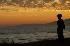 Boy by sea at sunset. Silhouetted young boy with protective helmet stood by sea with golden sunset background Stock Photos